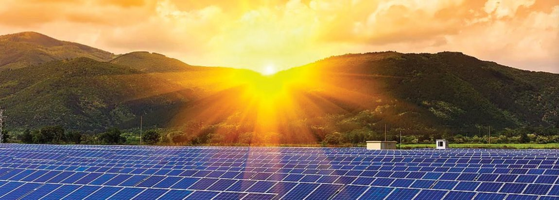 the sun rises over a mountain in Pennsylvania, shining on a field of solar panels